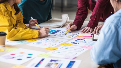 Tapeta Close up ux developer and ui designer brainstorming about mobile app interface wireframe design on table with customer breif and color code at modern office.Creative digital development agency.