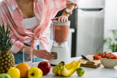 Tapeta cropped view of woman preparing delicious smoothie in blender