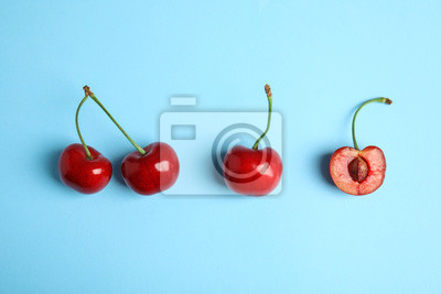 Tapeta Cut and whole sweet cherries on light blue background, top view