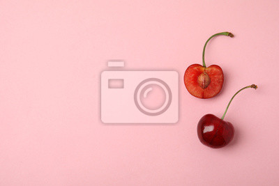 Tapeta Cut and whole sweet cherries on pink background, top view. Space for text