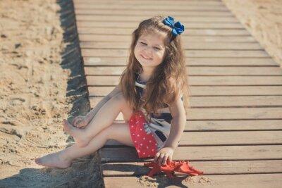 Cute little girl korzystających z czasu letniego na plaży po stronie morza Wszystkiego najlepszego z okazji gry z czerwoną gwiazdą i zabawki kotek na piasku noszenie nobby ubrania z brunetka włosy