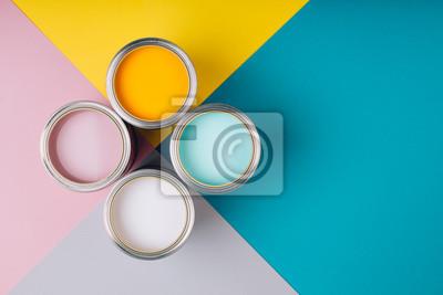 Tapeta Cztery otwarte puszki farby na jasnym tle symetrii. Żółte, białe, różowe, turkusowe kolory farb. Miejsce na tekst. Koncepcja renowacji.