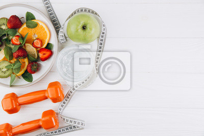 Tapeta Diet plan, menu or program, tape measure, water, dumbbells and diet food of fresh fruits on white background, weight loss and detox concept, top view