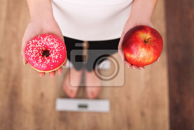 Tapeta Dieta. Kobieta pomiaru ciała ciężar na ważenie skali gospodarstwa Donut i jabłko. Słodycze są niezdrowe Junk Food. Diety, zdrowe odżywianie, styl życia. Utrata masy ciała. Otyłość. Widok z góry