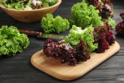 Tapeta Different sorts of lettuce on black wooden table