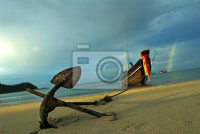Długi ogon łódź zakotwiczająca na piasku Tajlandzka plaża przeciw burzowemu niebu z tęczą w tle. Koh Pha Ngan, popularna miejscowość turystyczna.