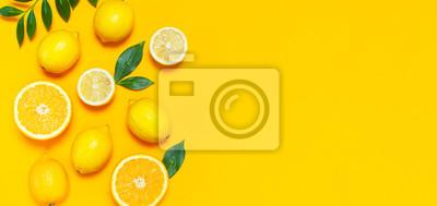 Tapeta Dojrzałe soczyste cytryny, pomarańczowe i zielone liście na jasnym żółtym tle. Owoc cytryny, minimalna koncepcja cytrusów, witamina C. Minimalistyczne kreatywne lato. Leżał płasko, widok z góry, miejs