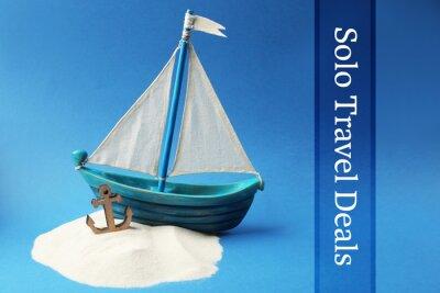 Drewniana łódź, kotwica i piasek na błękitnym tle. Koncepcja Columbus Day