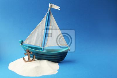 Drewniana łódź, kotwica i piasku na niebieskim tle. Koncepcja Columbus Day
