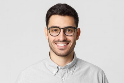 Tapeta Eyewear fashion. Headshot portrait of handsome smiling man dressed in gray shirt and wearing eyeglasses, isolated on studio background