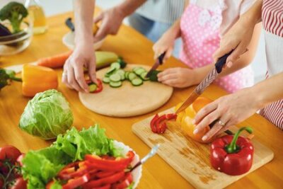 Tapeta Faceless. Family hands prepare fresh vegetables salad on the table in the kitchen. Mother's hands cut vegetables with a knife. Healthy eating