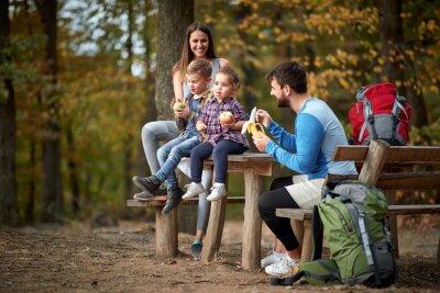 Tapeta Family with children having fruit snack on outing
