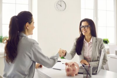 Tapeta Female bank manager shakes hands with a client during a meeting to sign a financial investment agreement. Happy financial advisor greets his female client after signing the insurance contract.