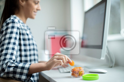 Tapeta Female Worker In Office Having Healthy Snack Of Dried Apricots At Desk