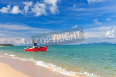 Fishing red boat on anchor near sand beach in Thailand