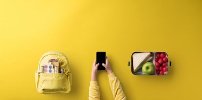 Tapeta Flat lay top view of child hands with smartphone, healthy snack and back to school concept.