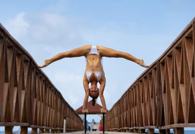 Tapeta Flexible female circus doing handstand upside down on the pier with sky background. Individuality, outstanding and originality.