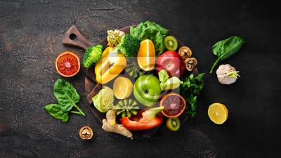 Tapeta Food containing vitamin C: Orange, lemon, apple, rose, garlic, broccoli, apple, kiwi, spinach. Top view. On a brown background.