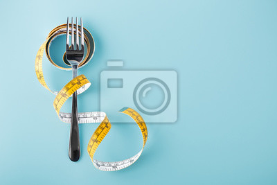 Tapeta Fork with measuring tape around, diet background