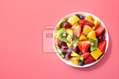 Fresh fruit salad on pink background