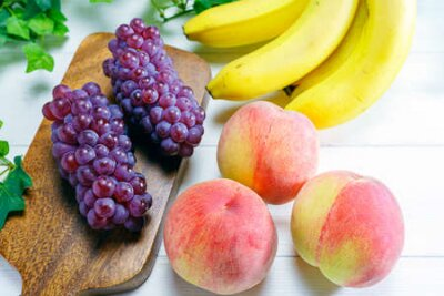 Tapeta Fresh peaches, grapes and bananas on wooden table