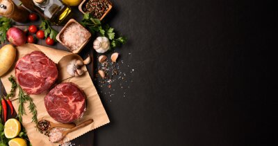 Tapeta Fresh raw pieces of beef meat with ingredients for cooking on panorama black stone background