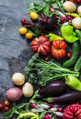 Tapeta Fresh seasonal vegetables food background. Aubergines, tomatoes, radishes, peppers, broccoli, potatoes, beets on a dark background, top view. Flat lay