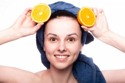 Tapeta funny woman after shower in a towel on her head holds an orange, skin care, vitamins, fruits