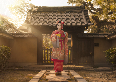 Tapeta Geisha in a kimono posing on a stone path in front of the gate of a traditional Japanese house surrounded by cherry blossoms and pine trees in the rays of sunset.
