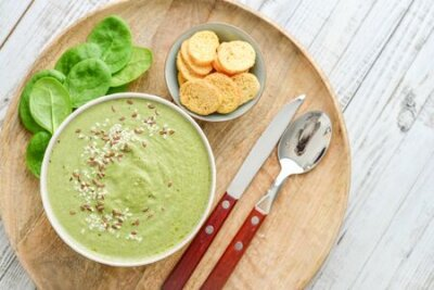 Tapeta Green broccoli soup with spinach on white wooden background, top view