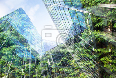 Tapeta green city - double exposure of lush green forest and modern skyscrapers windows