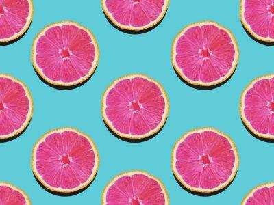 Tapeta Grejpfrut w płaskiej świeci Fruity wzór grejpfruta z różowym miąższem na turkusowym tle Widok z góry Nowoczesne mieszkanie lay świeca w stylu pop-art