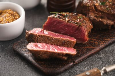 Tapeta Grilled beef fillet steaks with herbs and spices on wooden board. Two Fillet mignon. Fillet of beef.