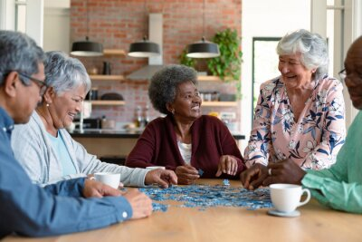 Tapeta Group of diverse senior male and female friends doing puzzles at home