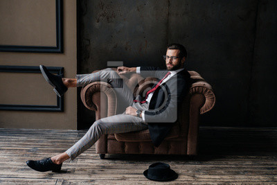 Tapeta handsome elegant businessman posing in armchair, hat lying on floor near, loft interior
