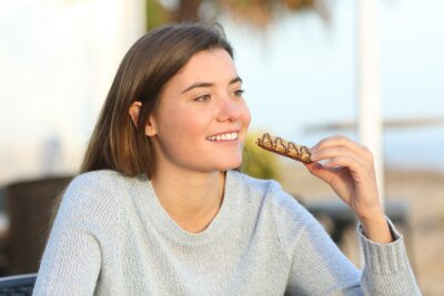 Tapeta Happy girl eating a snack in a coffee shop terrace