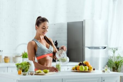 Tapeta happy woman with sportswear pouring smoothie in glass near fruits