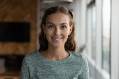 Tapeta Headshot portrait of smiling young Caucasian woman pose in modern office during work day. Profile close up picture of happy millennial female employee or worker show leadership success at workplace.