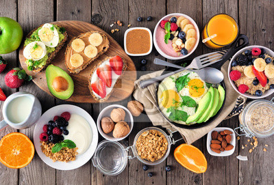 Tapeta Healthy breakfast table scene with fruit, yogurts, oatmeal, smoothie, nutritious toasts and egg skillet. Top view over a wood background.