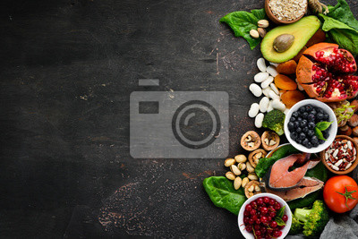 Tapeta Healthy food: Fish, blueberries, nuts, pomegranate, avocados, tomatoes, spinach, flax. Concept of Dietary Nutrition. Top view.
