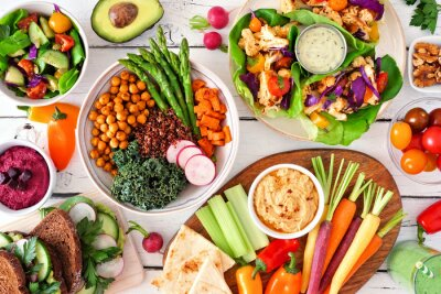 Tapeta Healthy lunch table scene with nutritious Buddha bowl, lettuce wraps, vegetables, sandwiches and salad. Top view over a white wood background.