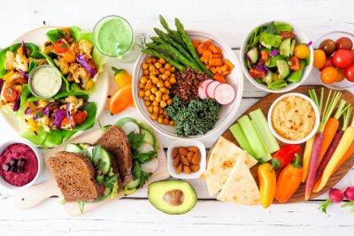 Tapeta Healthy lunch table scene with nutritious lettuce wraps, Buddha bowl, vegetables, sandwiches, and salad. Overhead view over a white wood background.