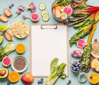 Tapeta Healthy smoothie ingredients around  clipboard with blank paper sheet on light table, top view, frame. Various fruits , vegetables and berries with almond, chia seeds and pine nuts. Vegan food