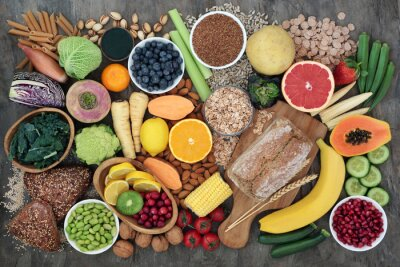 Tapeta High fibre super food with whole grain bread loaf and rolls, fruit, vegetables, whole wheat pasta, cereals, seeds and nuts. Foods omega 3, anthocyanins, antioxidants and vitamins. Top view.