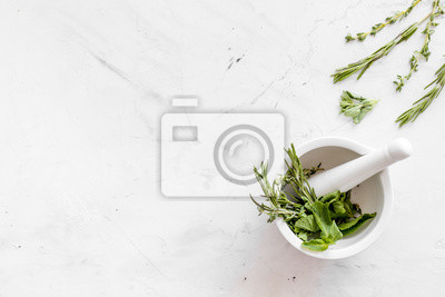 Tapeta Homeopathy with leaves and healing herbs for making oil on white marble background top view copyspace
