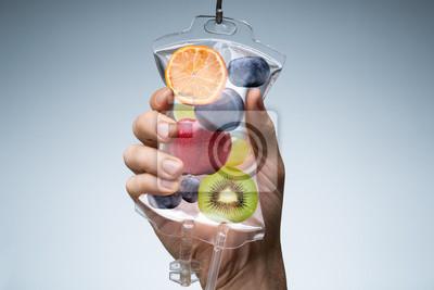 Tapeta Human Hand Holding Saline Bag With Fruit Slices Over Grey Background