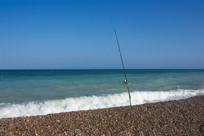 Image of a fishing rod anchored in sand of a deserted beach