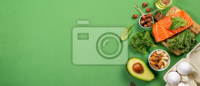 Tapeta Keto diet concept - salmon, avocado, eggs, nuts and seeds, bright green background, top view