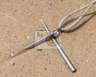 Kotwica z liną stałą metalu w piasku na brzegu morza
