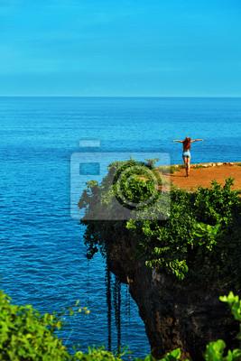 Krajobraz przyrody. Scenic widok Szczęśliwa kobieta za darmo z rękami do góry na pięknych tropikalnych zielony Cliff, Sea Rock na Paradise Island. Błękitnego nieba i oceanu w tle. Dekoracje Beauty. Wa